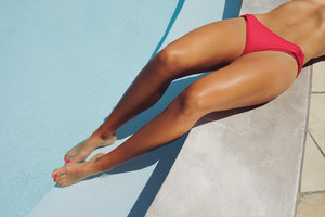 Overhead view of a pretty young woman wearing red bikini resting on the edge of a swimming pool. Woman sunbathing at poolside.