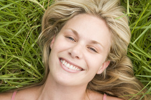 Overhead view of young woman lying on grass smiling to camera