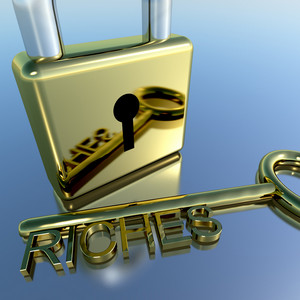 Padlock With Riches Key Showing Wealth Savings And Fortune