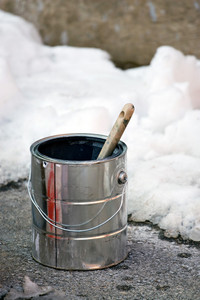 Paint can and brush on the ground outside in the winter.  Colder temperatures call for specialty paints made with different formulas.