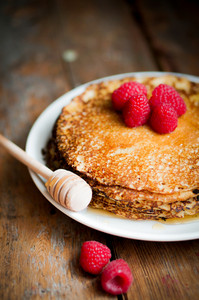 Pancakes With Maple Syrup And Raspberries On Wooden Background