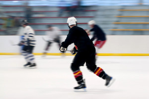 Panned motion blur of two hockey players skating down the ice rink.