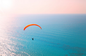Paraglider soaring over the sea