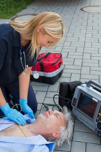 Paramedic examining unconscious elderly man lying on street