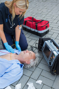 Paramedic examining unconscious elderly patient lying on street