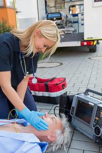 Paramedic helping injured senior patient lying on street