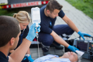 Paramedic holding drip while helping unconscious elderly man on street