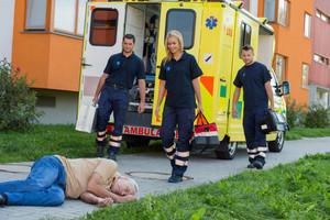 Paramedic team arriving to unconscious senior man lying on street