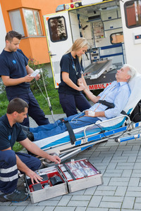 Paramedic team assisting injured senior man lying on stretcher outdoors
