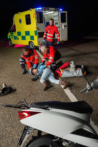 Paramedics assisting injured motorbike woman driver lying on road night