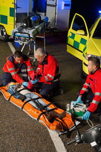 Paramedics assisting injured woman motorbike driver on stretcher at night