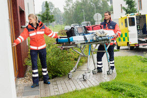 Paramedics carrying emergency stretcher ambulance house call visit door