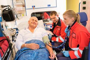 Paramedics checking patient pulse in emergency car ambulance medical chart