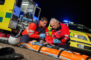 Paramedics giving firstaid to injured motorbike woman driver at night