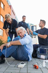 Paramedics giving firstaid to injured senior man sitting on street