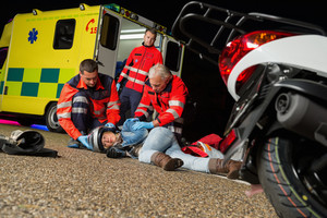 Paramedics helping injured motorcycle woman driver lying on road night