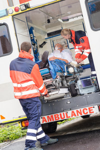 Paramedics putting patient man oxygen mask in ambulance car