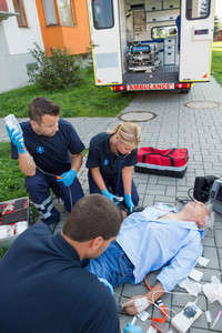 Paramedics treating injured senior man lying on street