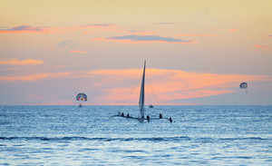 Parasailors in the ocean at sunset