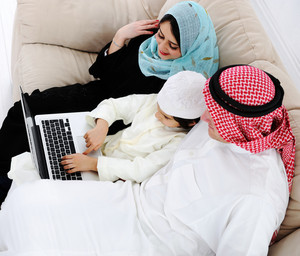 Parents and little boy at home with laptop computer
