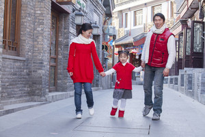 Parents walking with daughter dressed in holiday attire