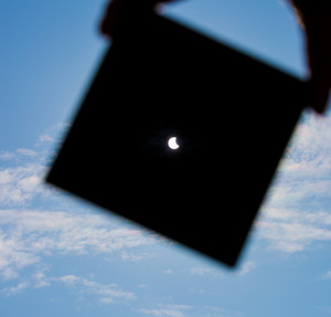 Partial Sun eclipse. Man covering a strong sunlight by dark plate and shows sun eclipse. man hand silhouette on blue sky.