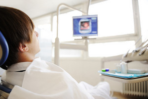Patient in modern hospital, dentist or something similar with monitor in front of him