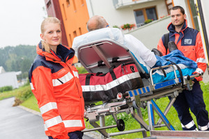 Patient on stretcher with paramedics ambulance aid emergency woman man