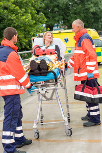 Patient talking with paramedics after accident  aid emergency arm injury
