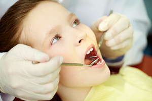 Patient with opened mouth being examined by a dentist