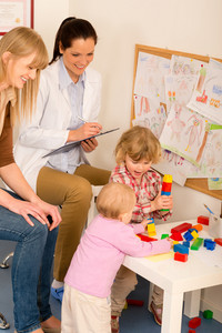 Pediatrician female observe children playing activity filling medical report
