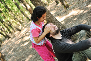 Peekaboo, daughter playing with her father in wonderfull forest