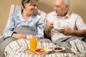 Pensioners drinking coffee and eating breakfast in the bed