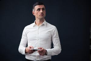 Pensive businessman holding smartphone