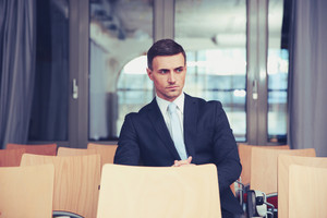Pensive businessman sitting at conference hall