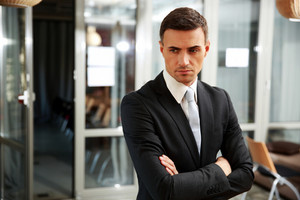 Pensive businessman standing at office