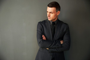 Pensive businessman with arms folded standing on gray background
