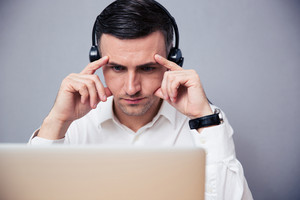 Pensive businessman working on laptop with headphones