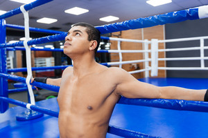 Pensive male boxer standing in gym and looking up