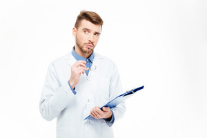 Pensive male doctor holding glasses and clipboard isolated on a white background