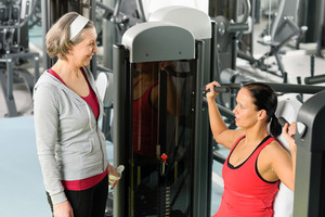 Personal trainer at fitness center showing exercise to senior woman