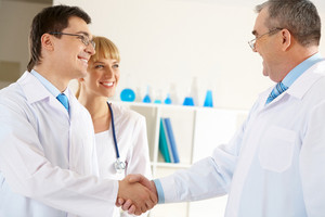 Photo of aged physician and young clinician handshaking with friendly nurse near by