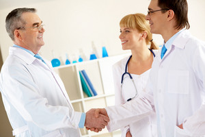 Photo of aged physician and young clinician looking at each other while handshaking with pretty nurse near by