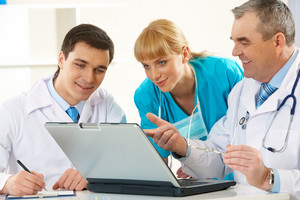 Photo of aged physician pointing at laptop display while explaining something to his colleagues