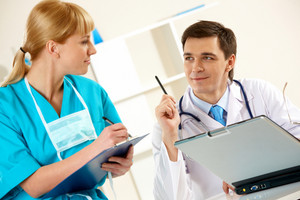Photo of confident physician looking at nurse while she making notes
