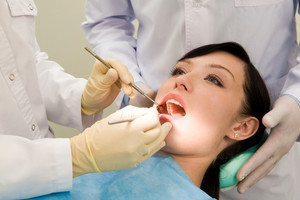 Photo of female patient with open mouth while her teeth being examined supported by assistant