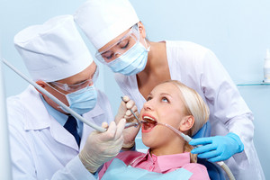 Photo of patient before healing teeth with dentist and assistant near by