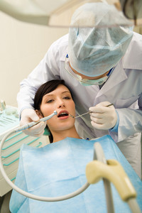 Photo of pretty girl with the dentist over her holding drilling instrument and mirror