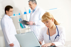 Photo of serious nurse with laptop planning work in working environment