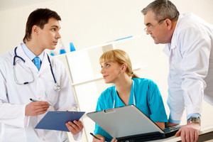 Photo of three clinicians having serious conversation in hospital